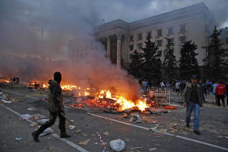 A protester walks past a burning pro-Russian tent camp near the trade union building in Odessa May 2, 2014. REUTERS/Yevgeny Volokin (UKRAINE - Tags: POLITICS CIVIL UNREST TPX IMAGES OF THE DAY)