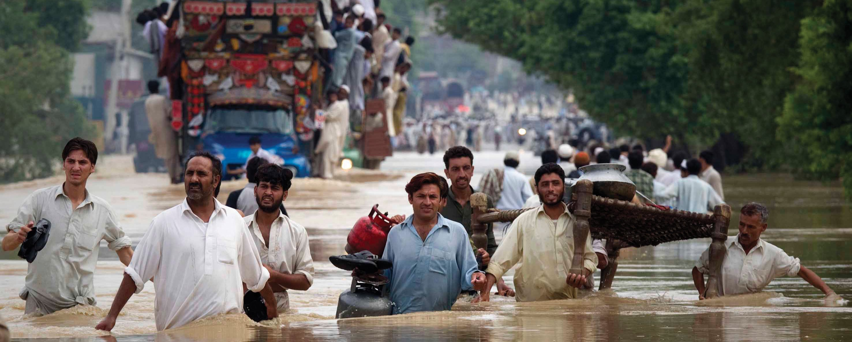Residents carry their belongings through a flooded road in Risalpur, located in Nowshera District, in Pakistan's Northwest Frontier Province July 30, 2010. About 150 people have been killed by flashfloods and bad weather in Pakistan in the last week, with the country's northwest and Baluchistan provinces bearing the brunt of the storms, officials said on Thursday. REUTERS/Adrees Latif (PAKISTAN - Tags: DISASTER ENVIRONMENT)